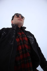handsome young man in sunglasses stands in a field in winter. stands on a hill and looks into the distance. the majestic sky in the background