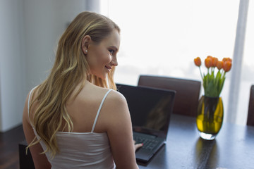Young woman typing on laptop rear view