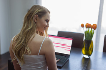 Young woman online chat on laptop looking over shoulder