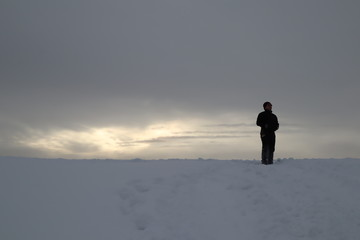 silhouette of man on top of mountain at sunset. figure of a man on a hill in winter. in the background the majestic sky and the sun breaking through the clouds