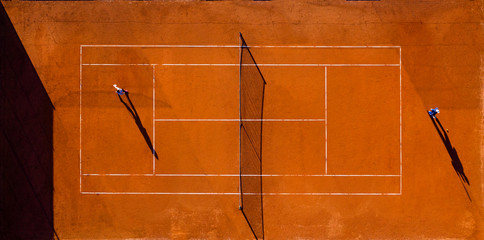 Aerial view of a tennis court with two players who are playing a match.