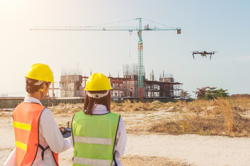 Two construction engineers working outdoors in construction site,Control the drones