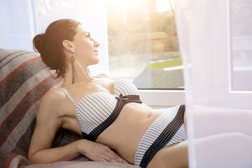 Happy brunette woman in lingerie as underwear lies relaxed on bed in front of a window