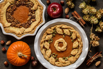 pumpkin pie with nuts, pumpkin seeds and Apple on dark background