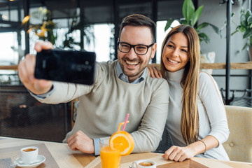 Young happy couple doing selfie in a cafe