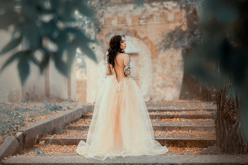 a mysterious dark-haired girl stands alone in a long elegant gold dress with an open back and a naked shoulder, the magnificent Cinderella escapes from the ball, a proud look, cool colors