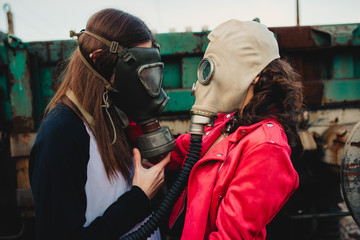 Side view of young hipsters in trendy wear and respirators standing near old construction
