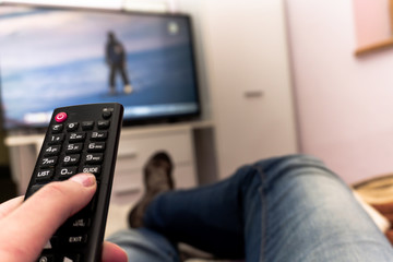 Remote control in hand before TV. Couch potato. Point of view shot. Woman holding remote control in hand.