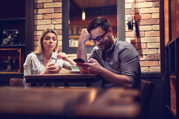 Young smiling couple in gorgeous restaurant. Man looking at phone. - Image