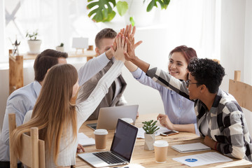 United happy multi-ethnic team give high five together share success