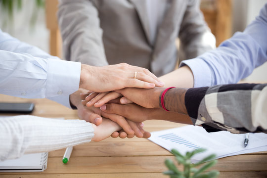 Stacked hands pile closeup, diverse business people holding hands together