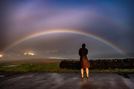 Lady observing very rare moonbow during the night above Staffin bay - Isle of Skye, Scotland