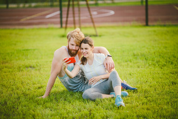 Sport and technology. Young in love heterosexual Caucasian couple resting after workout outdoors in park on lawn, green grass sitting in embrace and making selfie photo on smartphone camera at sunset