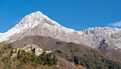 Old village on top of a hill with snowy mountain in the background, Pruno, Tuscany, Italy