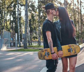 Young stylish loving couple kissing in the skatepark, enjoying spending time together at the summertime