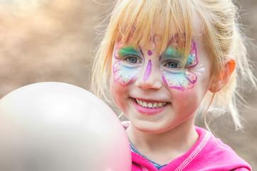 Glückliches geschminktes Mädchen beim Kinderkarneval auf einem Freizeitpark mit einem weißen Luftballon