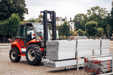 Forklift delivers metal profile from warehouse for construction of building