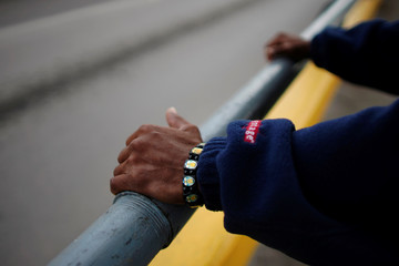Mexican Hernesto Gomez, wears a bracelet decorated with images of narco patron saint Jesus Malverde as he contemplates Rio Bravo over a bridge connecting Eagle Pass, Texas, with Piedras Negras, Mexico, in Piedras Negras