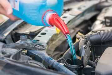Befüllen des Wischwasserbehälters mit Frostschutzmittel im Motorraum eines Autos