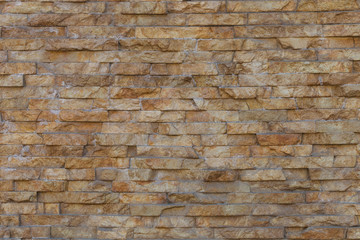 Natural stone granite pieces tiles for walls. Natural stone granite pieces tiles for walls. Wall of stone beige surface bricks as a background.