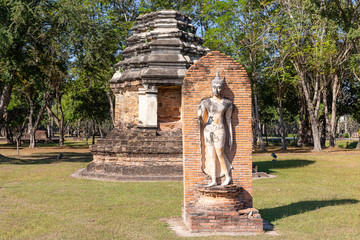Prang tower and sculpture of a deity next to Wat Traphang Ngoen in the Historical Park of Sukhothai, Thailand, Asia
