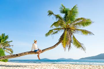 Wall Mural - Mann sitzt entspannt auf einer Kokospalme am Strand und schaut aufs Meer