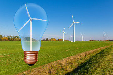 Light bulb with wind turbine inside on the background of blue sky and green field with turbines. Conceptual picture
