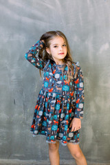 Funny little girl wearing nice blue dress. Isolated on grey
