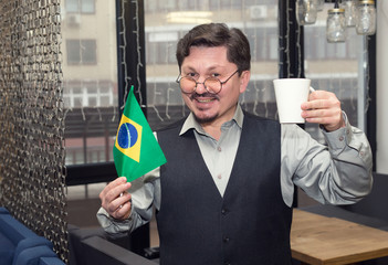 Mature man with a Brazil flag and a cup of coffee in his hands. South American happy man.
