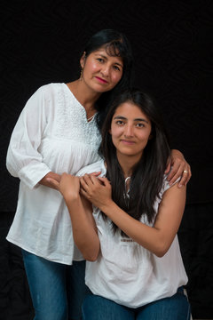 mexican mother and daughter black background