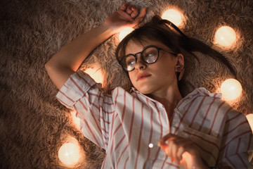 Hot young stylish woman in shirt and glasses lying on the soft bed with fairy lights at night