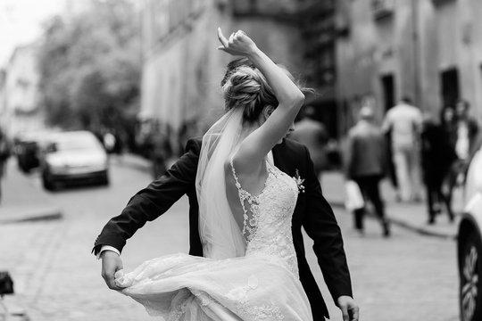 stylish bride and groom dancing and having fun in city street. happy luxury wedding couple holding hands in light. romantic sensual moment.  emotional man and woman. black white