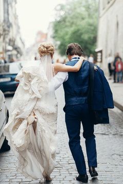stylish bride and groom walking in city street. happy luxury wedding couple holding hands in light and moving. romantic sensual moment.  back view at man and woman