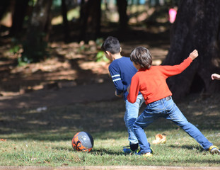 boys playing football in park