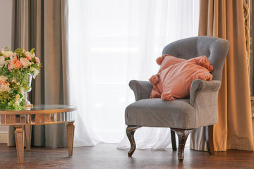 grey chair with pink pillows and flowers in the room