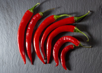 Red hot chili peppers on a black slate background close-up