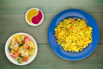 Asian healthy food. Rice (yellow) on a plate with vegetables. Eastern food on a wooden background