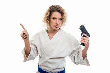 Portrait of female wearing martial arts holding shotgun