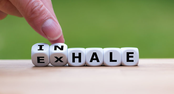 """Inhale,Exhale concept. Hand turns dice and changes the word """"INHALE"""" to """"EXHALE""""."""