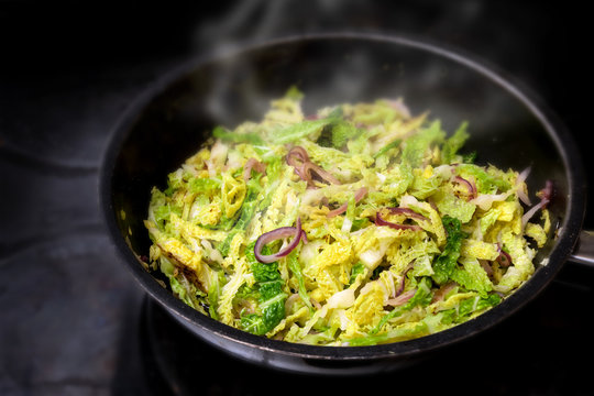 cooking green savoy cabbage with red onions in a black pan on a stove, healthy winter vegetable