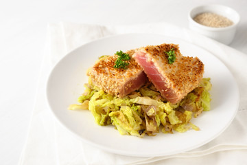 roasted tuna steak in sesame seeds with savoy cabbage vegetable, on a plate on a white table, copy space