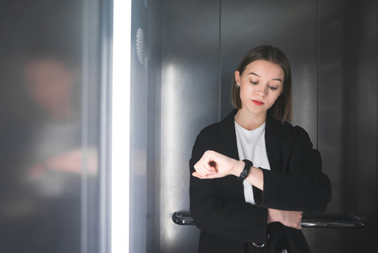 Female office worker is tired of waiting in the elevator. Young employee is looking at her watch bored waiting in the lift.