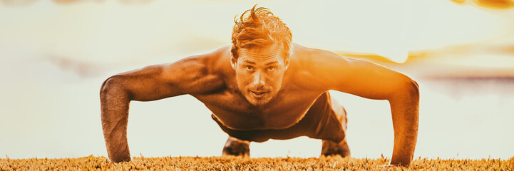 Fit man strong muscular exercise doing pushup workout outdoor in sunset glow panoramic banner.
