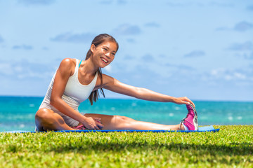 Fitness woman stretch legs doing warm-up before run workout training outdoor. Asian athlete stretching side hamstring muscle yoga stretched leg stretches exercises in outdoor gym.