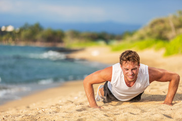 Fitness exercise man training arms doing push ups outdoor on beach.
