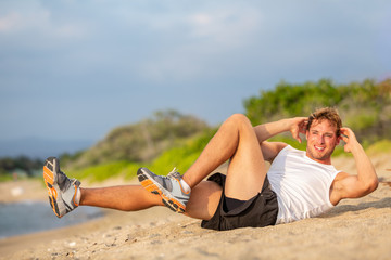 Exercise sit up fitness man doing situps outside in summer beach. Fit athlete working out cross training bicycle crunches to activate obliques mucles abs workout. Caucasian muscular sports model.