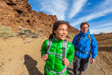 Happy hikers on mountain climb hike trekking with cold jackets and backpacks healthy active lifestyle. Young Asian woman with Caucasian man smiling walking outdoors.