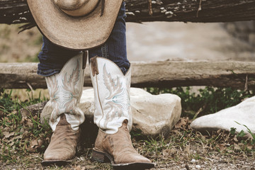 Western lifestyle shows woman in cowboy boots with straw hat on farm.