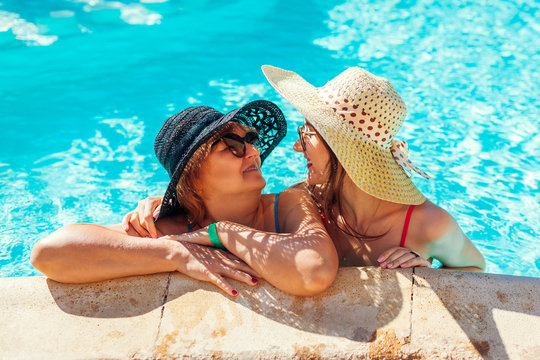 Senior woman relaxing with her adult daughter in hotel swimming pool. People enjoying vacation. Mother's day