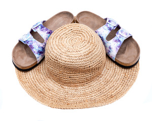 Purple Double Strap Sandals with a colorful print on the faux leather straps, with a soft micro suede foot bed and cork out-sole put on top of a stylish straw summer tan hat. On white background.